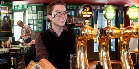 A young man wearing Tobii Pro Glasses eye tracker places an order in a bar.